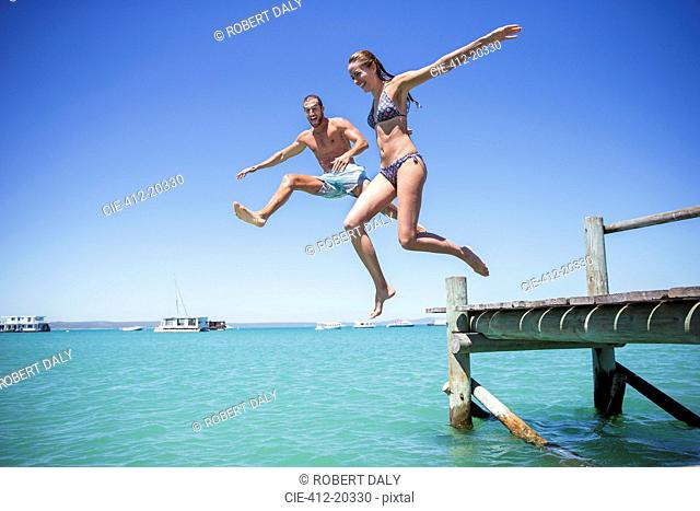 Couple jumping off wooden dock into water