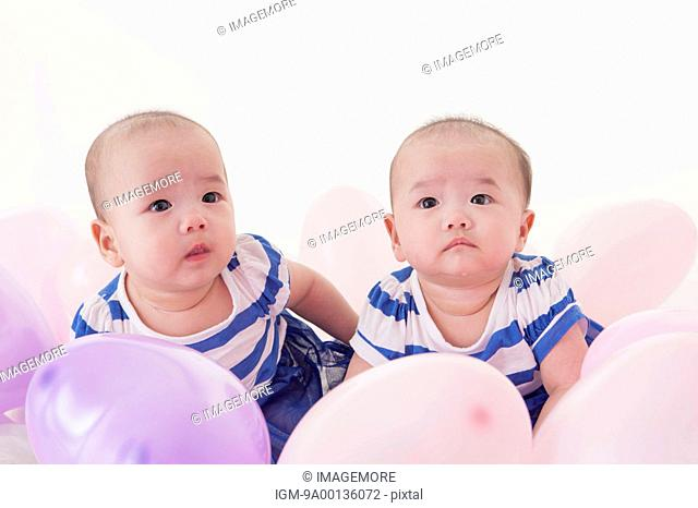 Cute twins looking away with balloon