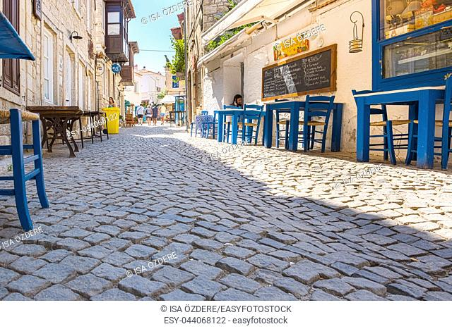 HDR Image-Unidentified People walk at a street with cafe and restaurant with tables and chairs at Alacati Town,popular destination for traveling and vacation in...