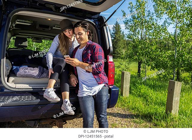 Young couple at their vehicle with the back open looking at a cell phone; Edmonton, Alberta, Canada