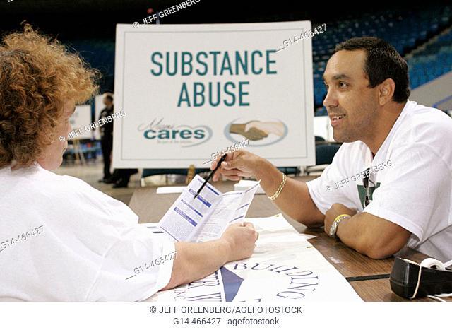 Arena, Miami Cares Day, free services, homeless, substance abuse, sign, help, Hispanic man, couselor. Miami. Florida. USA