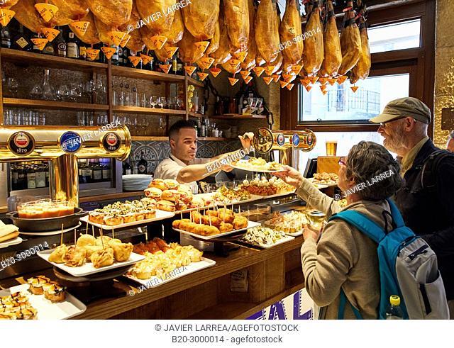 Waiter serving pintxos to tourists, Ham, Pintxos, Bar Restaurante Portaletas, Parte Vieja, Old Town, Donostia, San Sebastian, Gipuzkoa, Basque Country, Spain