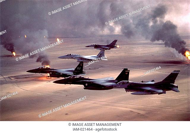 Operation Desert Storm 1991 F-16A Fighting Falcon, F-15E Strike Eagle, and F-15C Eagle fighter jets fly over Kuwait's burning oil fields