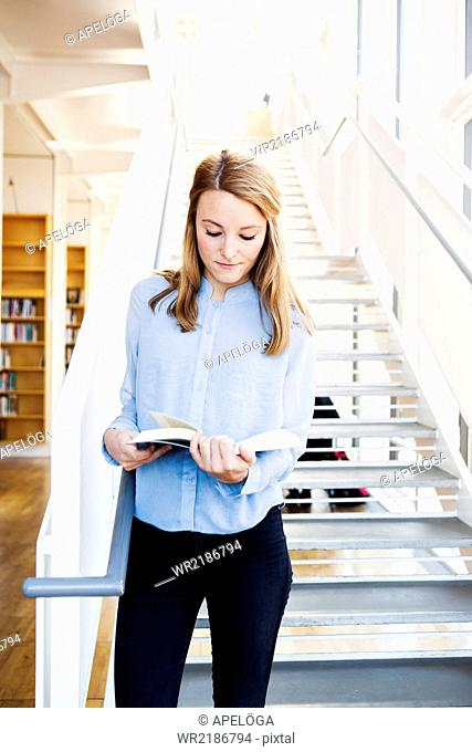 Young woman reading book while standing on steps in library