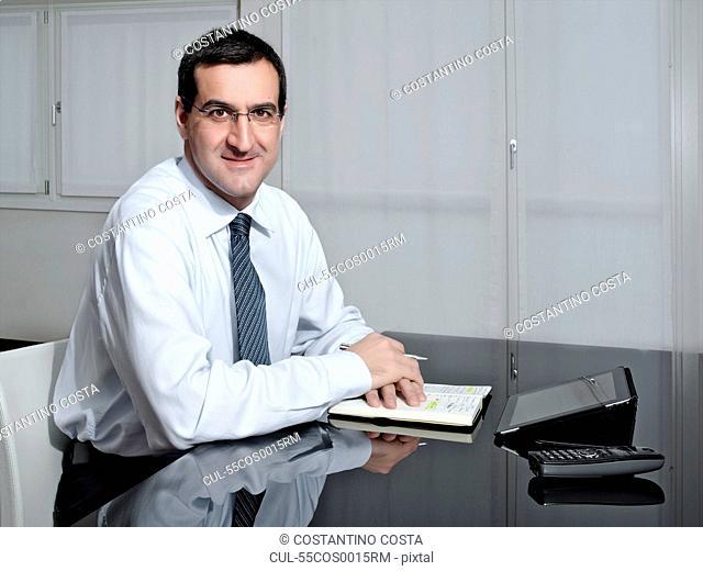Portrait of mature businessman at desk