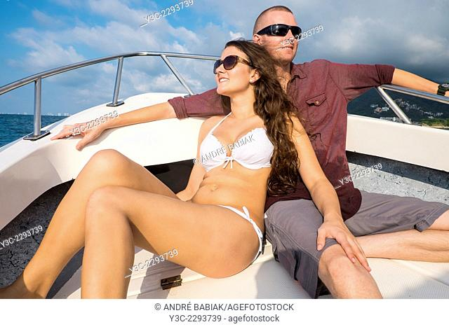 Young woman in bikini sitting next to a man on a fishing boat bow. Both are enjoying the ride on a sunny day