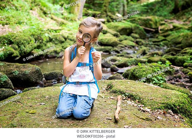 Little girl with magnifier crouching on rock in the woods watching a feather