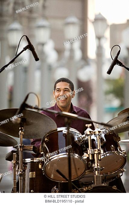 Mixed race man playing drums