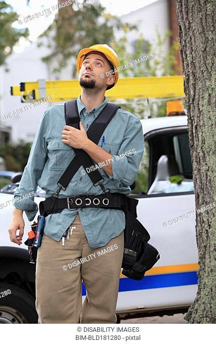 Caucasian worker walking under tree