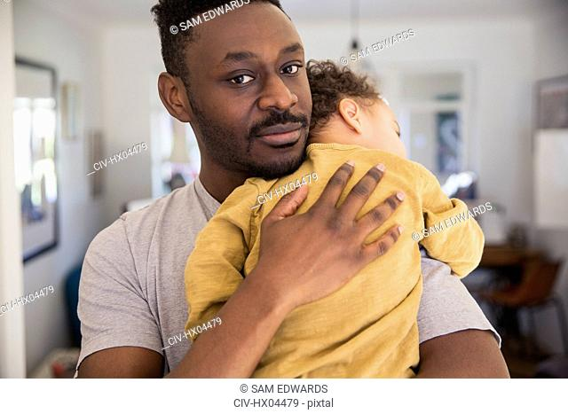 Portrait affectionate father holding tired baby son