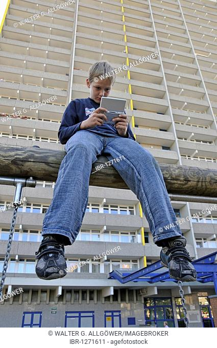 Boy, 9, playing with his Nintendo in front of a high-rise apartment building, satellite town of Chorweiler in Cologne, North Rhine-Westphalia, Germany, Europe