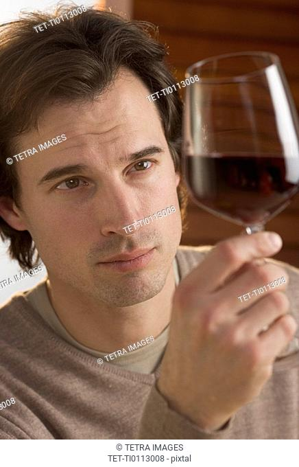 Closeup of man examining red wine