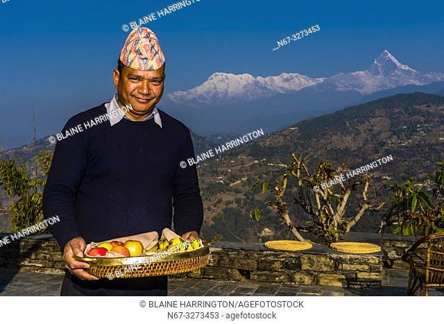 Staff member serving breakfast on the patio at Tiger Mountain Pokhara Lodge, Lekhnath (near Pokhara), Nepal