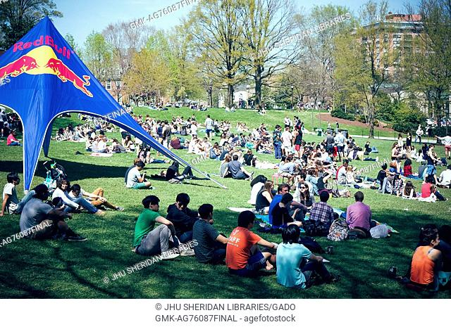 Dozens of students huddle and sunbathe on the grassy Beach, with drinks all around and a large Red Bull tent to the left, during Spring Fair