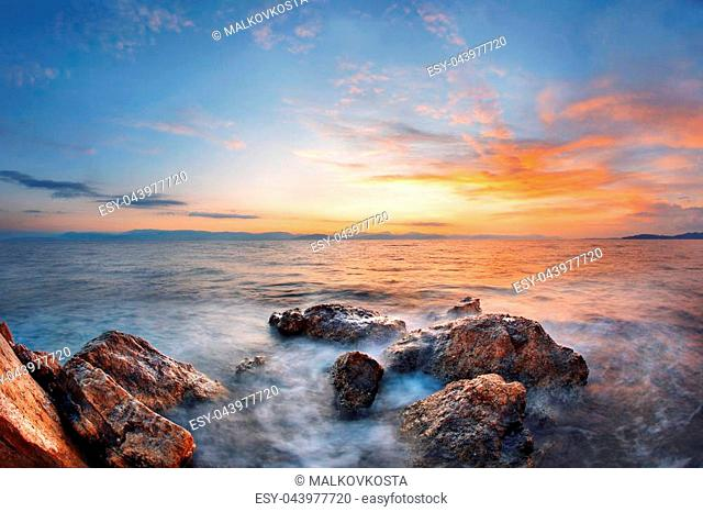 Colorful autumn sunrise on rock beach. Dramatic morning scene of the Ionian Sea, Corfu island location, Greece, Europe. Beauty of nature concept background