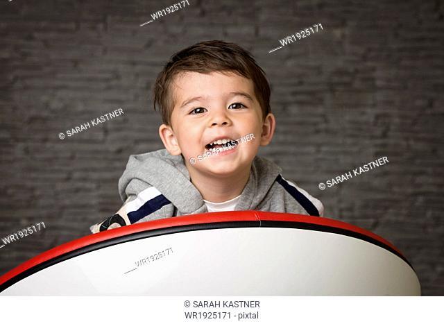 Little boy sitting in an armchair