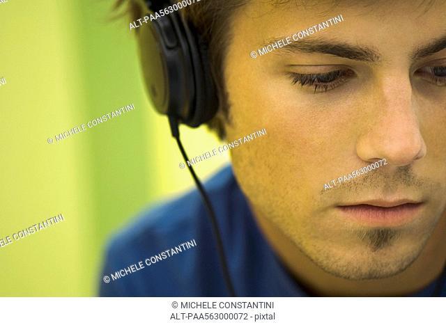 Young man listening to headphones, looking away