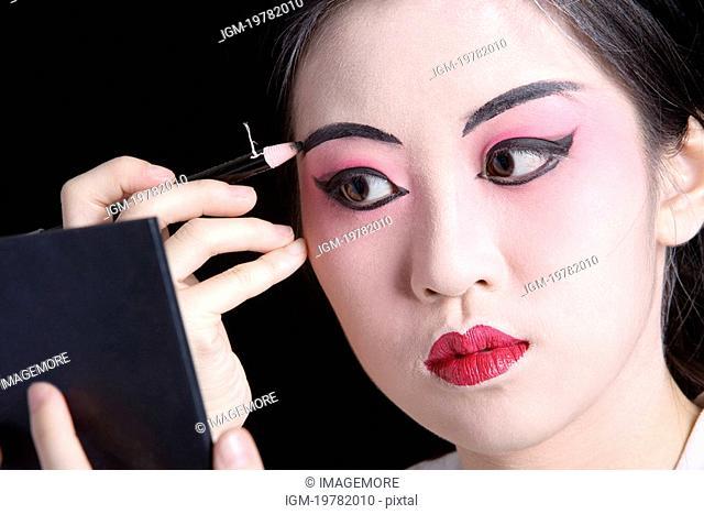 Beijing Opera performer applying eyebrow in mirror