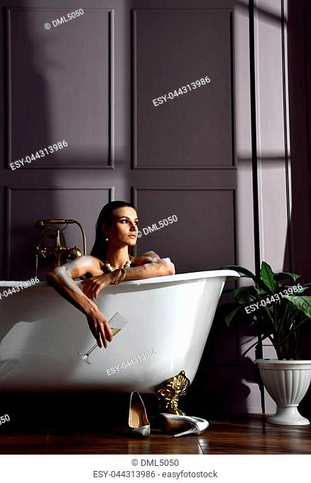 Young beautiful woman sitting in bathroom in expensive bathtub bath drinking champagne looking at the corner on dark background
