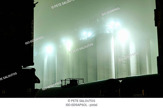 Misty view of industrial storage tanks between locomotive at night, Seattle, Washington, USA