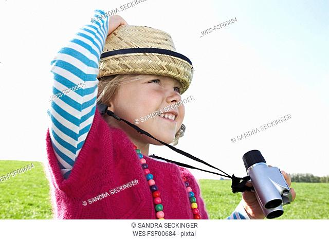 Girl with binoculars on meadow