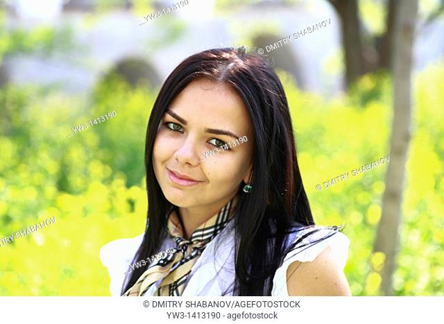 Pretty young 20-25 years woman in the garden among grass flowers