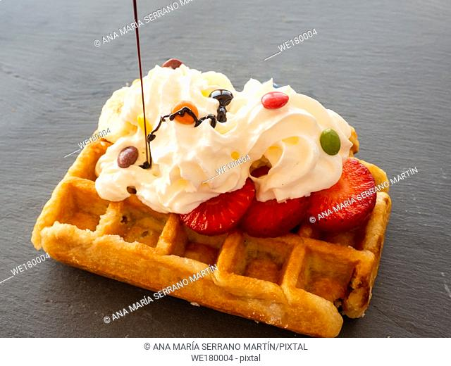 Chocolate syrup falling on a Belgian waffle with cream and colorful chocolates on pieces of strawberry on a slate plate
