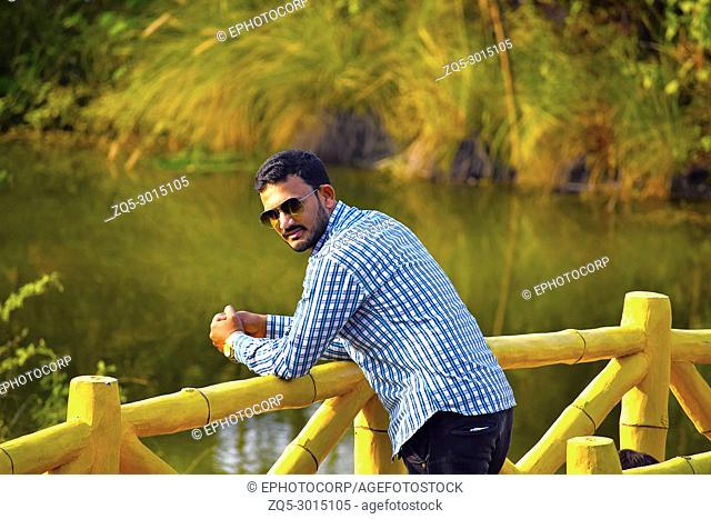 Man on a wooden bridge near lake, Pune, Maharashtra