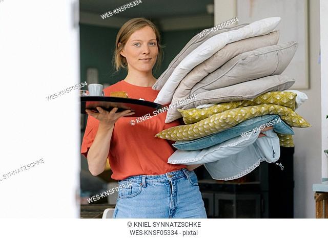 Portrait of young woman holding tray and cushions in a cafe