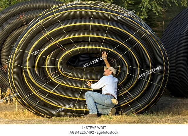 A farmer inspects a role of tubing; United States of America