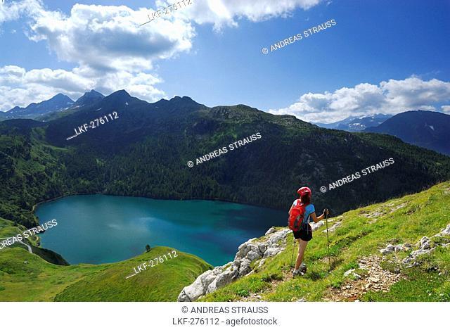 Woman hiking above reservoir Lago Ritom, Ticino Alps, Canto of Ticino, Switzerland