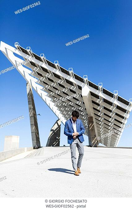Young businessman walking outdoors checking the time