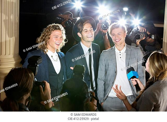Smiling celebrities being interviewed and photographed by paparazzi photographers at event