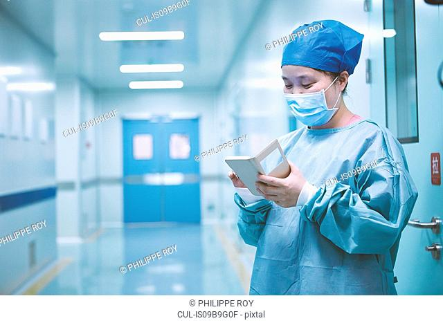 Female surgeon looking at smartphone in maternity ward operating theatre corridor
