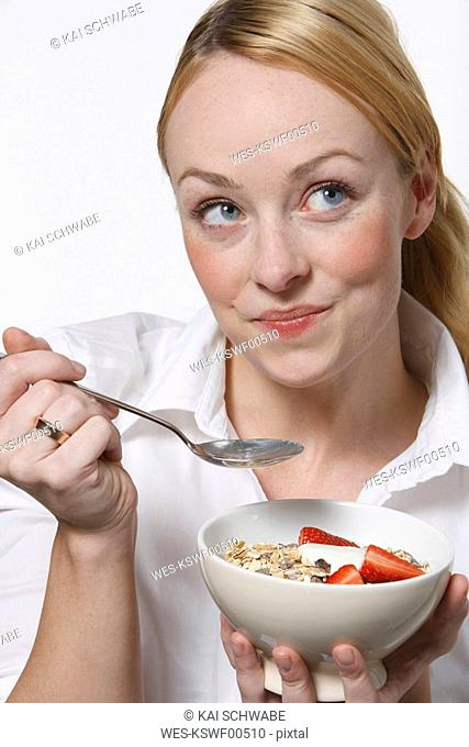 Young woman eating muesli, smiling, portrait