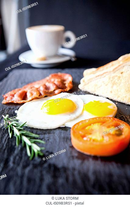 Toast with bacon, fried eggs and tomato breakfast on slate
