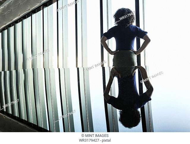 Black businesswoman reflected on the glass top of an office desk in front of a bank of windows