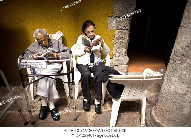 Luz Maria Rodriguez, 92, and Laura Ruiz Barrios, 75, read books in the patio of Our Lady of Guadalupe Home for the Elderly, Mexico City