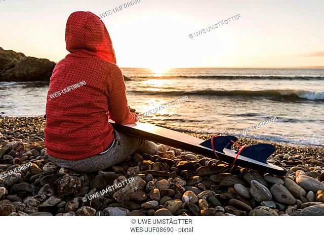 France, Bretagne, Crozon peninsula, woman sitting on stony beach at sunset with surfboard