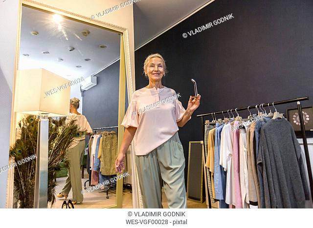 Smiling senior woman walking in a boutique reflected in mirror