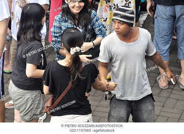 Ubud (Bali, Indonesia): a local seller pushing a Chinese tourist, in a playfully way, to buy his merchandise