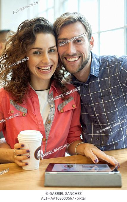 Couple using digital tablet in cafe, portrait