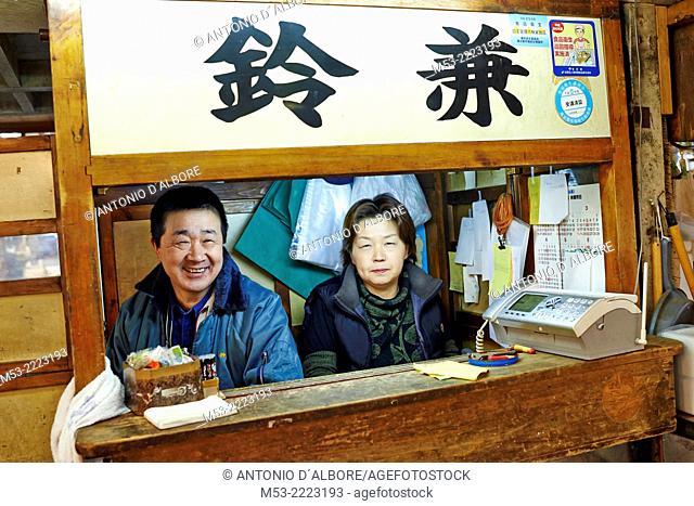 A japanese man and woman at the cashier desk of ther fish trading company. Tsukiji Fish Market. Chuo Ward. Tokyo. Japan