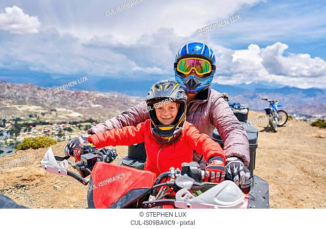 Mother and son on top of mountain, using quad bike, La Paz, Bolivia, South America