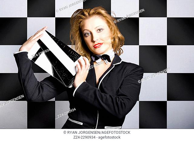 Fashion girl concept of a beautiful young woman posing on chequered black and white interior with bag. Evening accessories