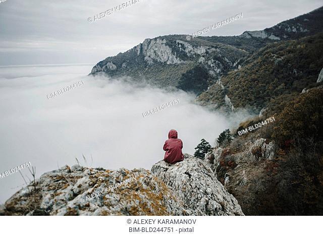 Distant Caucasian woman sitting on rock watching fog on ocean