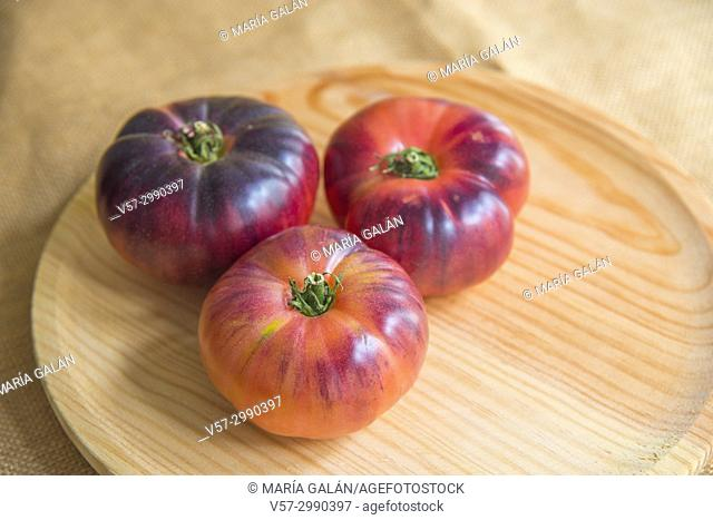 Three blue sea tomatoes on a wooden dish. Still life