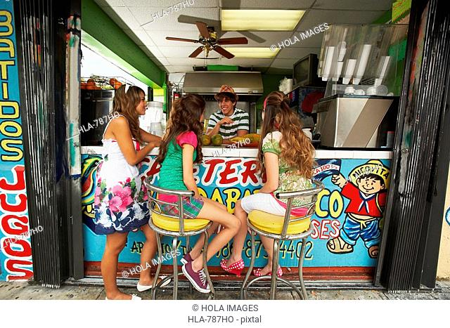 Three teenage girls talking with a bartender in a juice bar
