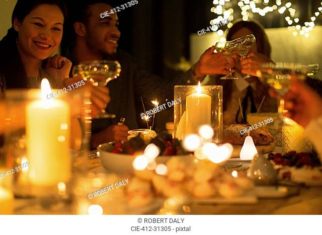 Friends toasting champagne glasses at candlelight Christmas table