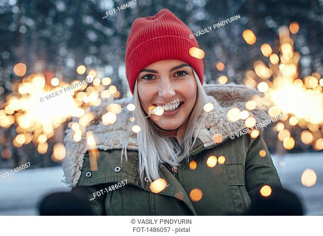 Portrait of smiling woman holding sparklers during winter